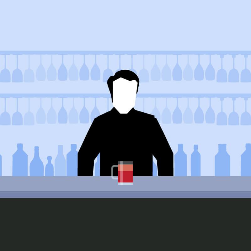 Man standing behind a drinks bar with a red cocktail in front of him
